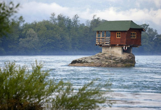 A house built on a rock on the river Drina is seen near the western Serbian town of Bajina Basta, about 160km (99 miles) from the capital Belgrade May 22, 2013. The house was built in 1968 by a group of young men who decided that the rock on the river was an ideal place for a tiny shelter, according to the house's co-owner, who was among those involved in its construction. (Photo by Marko Djurica/Reuters)