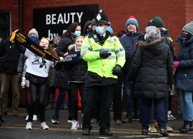 A policeman stands in-front of Newport fans prior to the FA Cup Third Round match between Marine and Tottenham Hotspur at Rossett Park on January 10, 2021 in Crosby, England. Sporting stadiums around England remain under strict restrictions due to the Coronavirus Pandemic as Government social distancing laws prohibit fans inside venues resulting in games being played behind closed doors. (Photo by Tottenham Hotspur FC/Tottenham Hotspur FC via Getty Images)