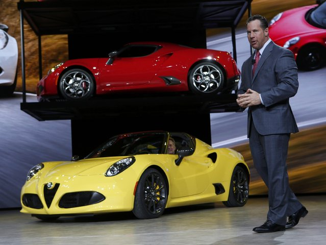Reid Bigland, President and CEO of Alfa Romeo North America, speaks next to a 2014 Alfa Romeo 4C (top) and a 2015 4C Spyder during the first press preview day of the North American International Auto Show in Detroit, Michigan January 12, 2015. (Photo by Rebecca Cook/Reuters)