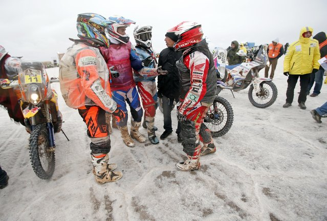 Competitors speak before the start of the 8th stage of the Dakar Rally 2015 on the Salar de Uyuni salt flat, from Uyuni to Iquique, January 12, 2015. (Photo by Jean-Paul Pelissier/Reuters)