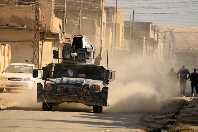 A military vehicle of Iraqi security forces is seen at Hammam al-Alil, south of Mosul, during a battle with Islamic State militants, Iraq November 6, 2016. (Photo by Thaier Al-Sudaini/Reuters)