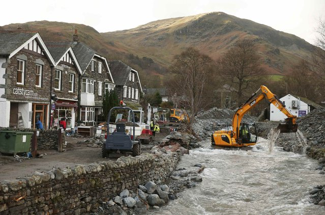 An excavator dredges the riverbed after it burst it's banks, flooding the village of Glenridding in North West England, December 10, 2015. (Photo by Phil Noble/Reuters)