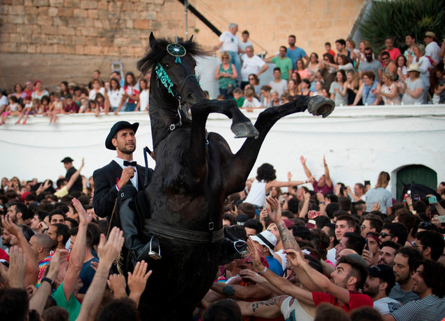 A horse rears in the crowd during the traditional San Juan (Saint John) festival in the town of Ciutadella, on the Balearic Island of Menorca, on the eve of Saint John's day on June 24, 2018. During the island's San Juan festival, held each year on June 23 and 24, Minorcan race horses gallop and prance on their hind legs through the streets of Ciutadella to honor of the town's patron saint. (Photo by Jaime Reina/AFP Photo)