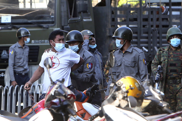 A man is held by police during a crackdown on anti-coup protesters holding a rally in front of the Myanmar Economic Bank in Mandalay, Myanmar on Monday, February 15, 2021. (Photo by AP Photo/Stringer)