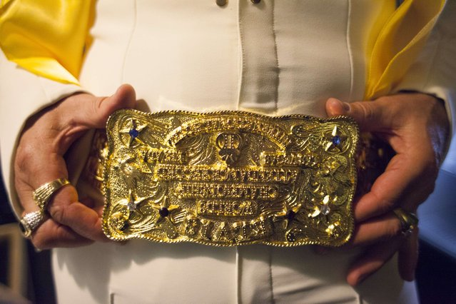 A participant shows off a belt buckle during the 20th annual Seattle Invitationals, an amateur Elvis impersonator competition, in Seattle, Washington January 23, 2015. The event drew hundreds of spectators for 20 contestants at the Crocodile, a venue in Seattle's Belltown neighborhood. (Photo by David Ryder/Reuters)