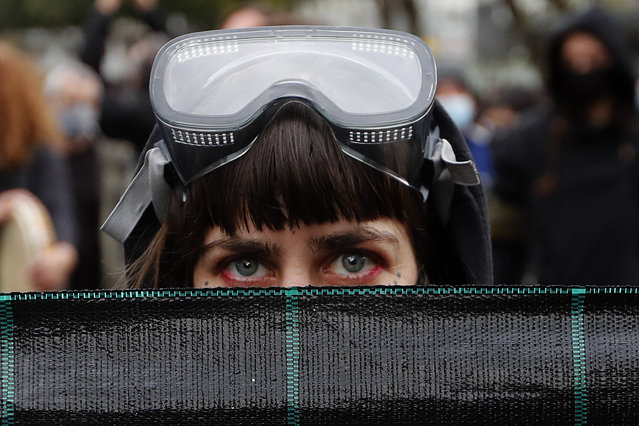 A protestor with a diving mask on her head, holds a banner during a protest in the capital Nicosia, on Saturday, February 20, 2021, against the corruption within the country's politicians, as well as fatigue over restrictions to curb COVID-19 infections. The demonstration that drew an estimated 3,000 people came a week after police were strongly criticized for resorting to disproportionate force by using a water canon, stun grenades and pepper spray to disperse a crowd of a few hundred left-wing protesters voicing their opposition to corrupt politicians. (Photo by Petros Karadjias/AP Photo)
