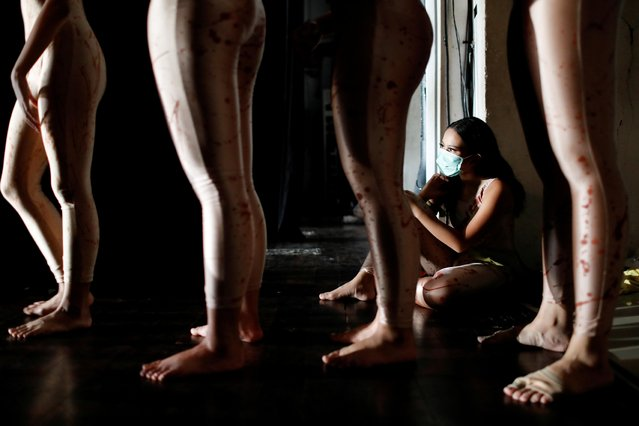 """A dancer wearing a protective mask to curb the spread of the coronavirus disease (COVID-19), sits during a virtual dance performance titled """"The Story of Man: In Search of A New Ideal"""" by Namarina Youth Dance, at the Jakarta Art Building, Indonesia, February 21, 2021. (Photo by Willy Kurniawan/Reuters)"""