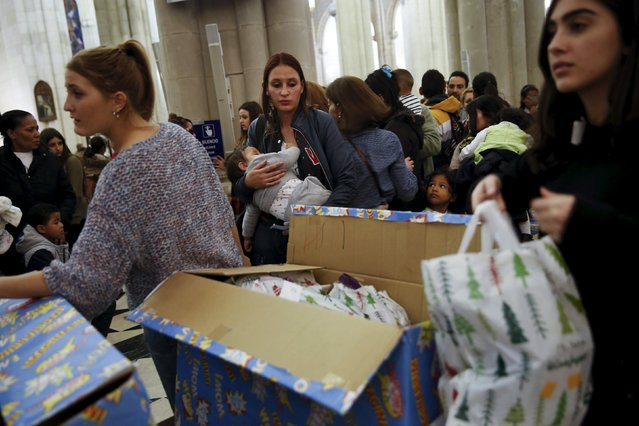 People wait in line during a distribution of free toys for low-income families at Almudena Cathedral in Madrid, Spain, December 22, 2015. (Photo by Susana Vera/Reuters)