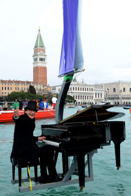 Pianist Paolo Zanarella appears to hover with the help of a crane in front of St. Mark square, as he performs during one of the highlights of the Venice Carnival, in Venice, Italy, Sunday, February 1, 2015. The Venice carnival in the historical lagoon city attracts people from around the world. (Photo by Sebastiano Casellati/AP Photo)