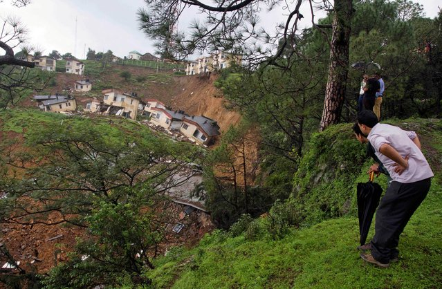 People look at buildings damaged by a landslide in Dharmsala, India, on August 7, 2013. Fearing more landslides, the nearby village of 60 residents were evacuated. No injuries were reported. (Photo by Ashwini Bhatia/Associated Press)