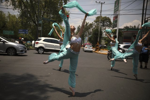 """Ballerinas dance in the middle of a street during a red traffic light in Mexico City, Saturday, July 28, 2018. In this sprawling megalopolis notorious for its clogged streets, a theater company sent out tutu-clad dancers out to delight motorists at snarled intersections with snippets from ballet classics like """"The Nutcracker"""" and """"Swan Lake"""" all in the 58 seconds it takes for the light to go from red to green. (Photo by Emilio Espejel/AP Photo)"""