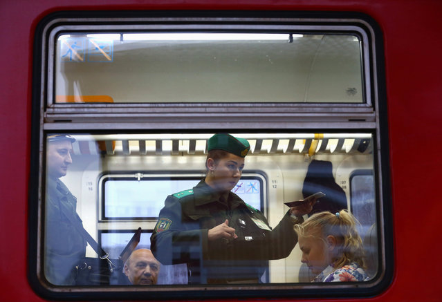 A Belarussian border guard checks a passenger's passport in a train after it arrived from Lithuania, at the railway station Gudogai, Belarus, November 22, 2016. (Photo by Vasily Fedosenko/Reuters)