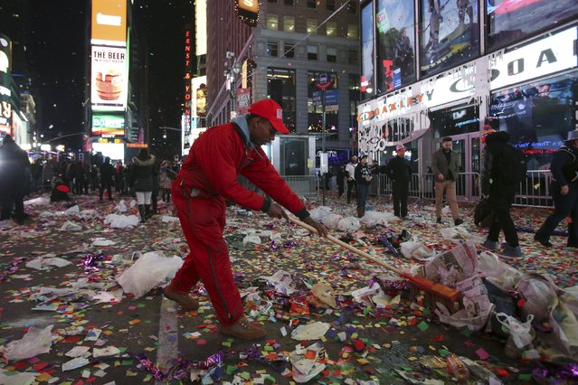 A worker cleans up confetti and garbage after New Year celebrations in Times Square in the Manhattan borough of New York January 1, 2016. (Photo by Andrew Kelly/Reuters)