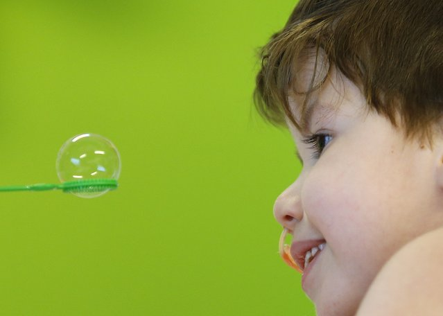Mohamed, 5, looks at a soap bubble at the pediatric department of the Hopital Erasme at the Universite Libre de Bruxelles (ULB), in Brussels, January 22, 2015. (Photo by Yves Herman/Reuters)