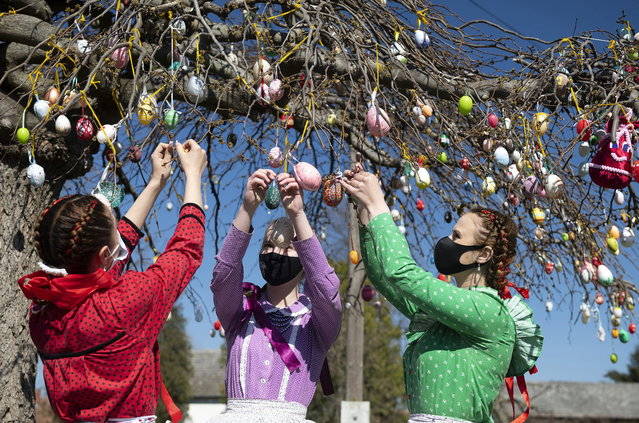 Dressed in folk costumes, young women decorate a tree with painted Easter eggs in Dombrad, Hungary, Monday, April 5, 2021. (Photo by Attila Balazs/MTI via AP Photo)