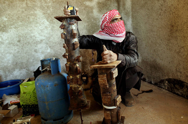 A bomb maker from Abu Suleiman's group of rebel fighters wires pipe bombs, which are detonated in specific areas to cut access to their mountainous stronghold in the northern Syrian province of Idlib, on March 20, 2012. Abu Suleiman, who finances the weapons for the unit which carries his name, has assembled one of the multitude of armed groups fighting the regime. (Photo by Frederic Lafargue/AFP Photo)