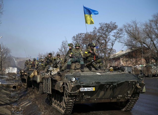 Members of the Ukrainian armed forces ride on armoured personnel carriers (APC) near Debaltseve, eastern Ukraine, February 12, 2015. (Photo by Gleb Garanich/Reuters)