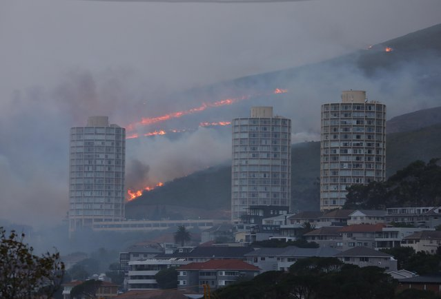 Flames are seen close to the city fanned by strong winds after a bushfire broke out on the slopes of Table Mountain in Cape Town, South Africa, April 19, 2021. (Photo by Mike Hutchings/Reuters)