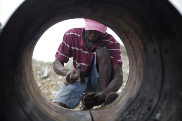 Sony Lonrisme cuts a discarded oil barrel in Noailles, an artisan's village in Croix de Bouquets, outskirts of Port-au-Prince, Haiti February 13, 2015. (Photo by Andres Martinez Casares/Reuters)