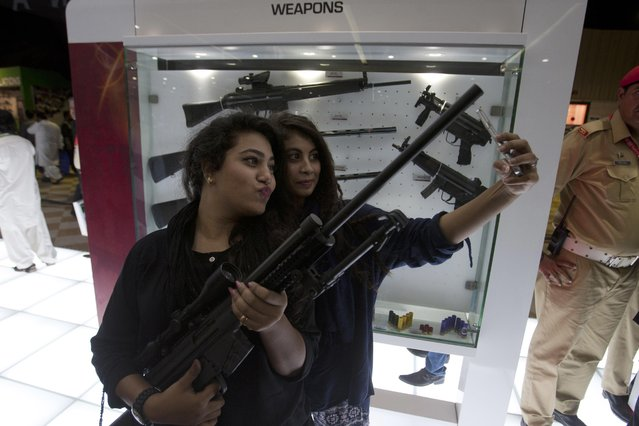 Pakistan girls make selfies holding a Pakistan-made weapon displayed at the four-day International Defence Exhibition and Seminar (IDEAS) 2016 in Karachi, Pakistan, Wednesday, November 23, 2016. (Photo by Shakil Adil/AP Photo)