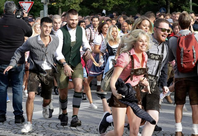 People run to enter the 185th 'Oktoberfest' beer festival in Munich, Germany, Saturday, September 22, 2018. The world's largest beer festival will be held from Sept. 22 until Oct. 7, 2018. (Photo by Matthias Schrader/AP Photo)