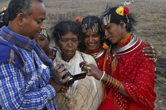 In this Saturday, February 21, 2015 photo, members of India's Dongria tribe watch their pictures in a visitor's camera during the two-day long Niyamraja Festival atop the Niyamgiri hills near Lanjigarh in Kalahandi district, Orissa state, India. (Photo by Biswaranjan Rout/AP Photo)