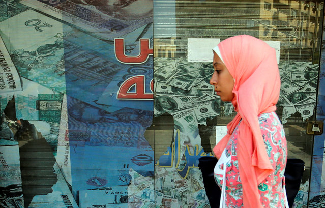 A woman walks past a money exchange bureau showing images of the U.S dollar with Egyptian pound and other foreign currency in Cairo, Egypt, October 12, 2016. (Photo by Amr Abdallah Dalsh/Reuters)