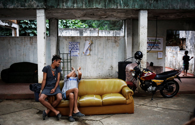 Teflon (L), 19, and Gaby, 18, who are among members of lesbian, gay, bisexual and transgender (LGBT) community, that have been invited to live in a building that the roofless movement has occupied, sit on a sofa, in downtown Sao Paulo, Brazil, November 17, 2016. (Photo by Nacho Doce/Reuters)