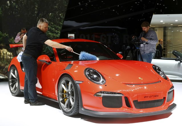 An employee dusts off the new Porsche 911 GT3 RS is seen during the second press day ahead of the 85th International Motor Show in Geneva March 4, 2015.  REUTERS/Arnd Wiegmann