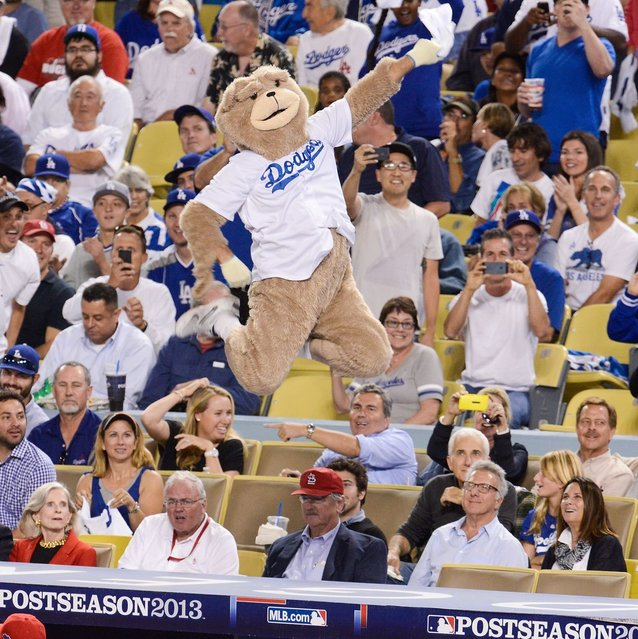 Dustin Hoffman watches an unoffical dancing bear mascot perform at Game Three of the National League Championship Series at Dodger Stadium on October 14, 2013 in Los Angeles, California. (Photo by Noel Vasquez/Getty Images)