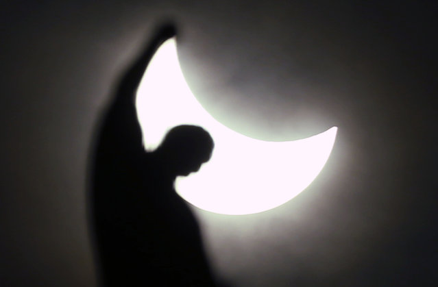 The sun is seen during a partial eclipse over a statue of the Duomo gothic cathedral in Milan, Italy, Friday, March 20, 2015. An eclipse is darkening parts of Europe on Friday in a rare solar event that won't be repeated for more than a decade. (Photo by Luca Bruno/AP Photo)
