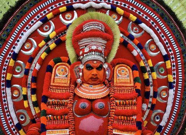 An artist dressed as the Hindu goddess Raktha Chamunda waits to perform during the Theyyam ritual in Somwarpet town in the southern Indian state of Karnataka March 17, 2015. Theyyam is a form of worship and is celebrated mostly in southern parts of the country. (Photo by Abhishek N. Chinnappa/Reuters)