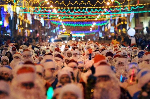 Belarus locals dressed as Father Frost and Snow Maidens march along a street during a traditional Christmas parade in Minsk on December 24, 2016. (Photo by Sergei Gapon/AFP Photo)