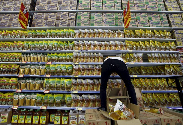 A worker arranges cooking oil at a Hypermart supermarket in Jakarta in this October 7, 2010 file photo. Indonesia is expected to report consumer confidence data this week. (Photo by Reuters/Beawiharta)