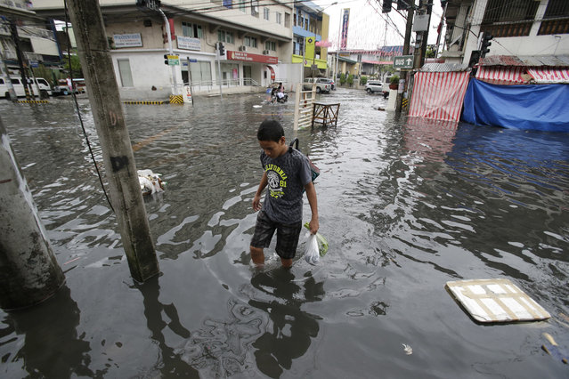 A man wades along a flooded street caused by rains from Typhoon Nock-Ten in Quezon city, north of Manila, Philippines on Monday, December 26, 2016. (Photo by Aaron Favila/AP Photo)