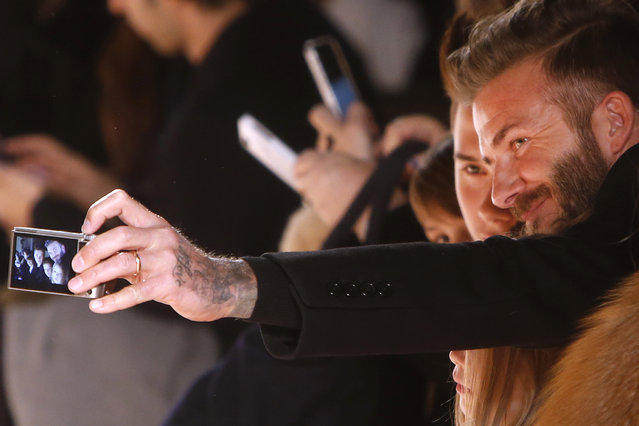 British soccer star David Beckham takes a photo with his children in the front row after the Victoria Beckham Fall 2015 collection show during Fashion Week, Sunday, February 15, 2015, in New York. (Photo by Jason DeCrow/AP Photo)