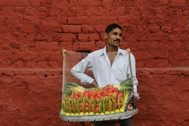 A street food vendor waits for customers on a footpath in New Delhi, India, November 27, 2018. (Photo by Anushree Fadnavis/Reuters)