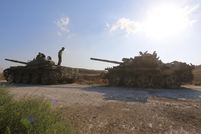 """Fighters from an alliance of insurgents known as the """"Army of Fatah"""" (Islamic Conquest) stand on tanks that belonged to forces loyal to Syria's President Bashar al-Assad in the village of al-Ziyara, after they took control of the village, in Hama province, Syria August 10, 2015. (Photo by Ammar Abdullah/Reuters)"""