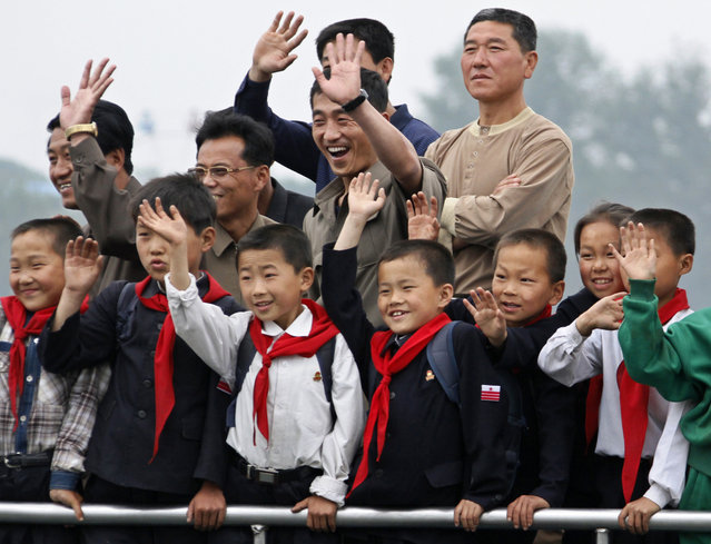 North Korean children and their parents wave to Chinese residents as they take a tour on a boat to celebrate International Children's Day on the Yalu River near the North Korean town of Sinuiju, opposite the Chinese border city of Dandong, June 1, 2011. (Photo by Jacky Chen/Reuters)