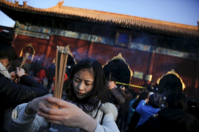 People burn incense and pray for good fortune on the first day of the Lunar New Year of the Monkey at Yonghegong Lama Temple in Beijing, China, February 8, 2016. (Photo by Damir Sagolj/Reuters)