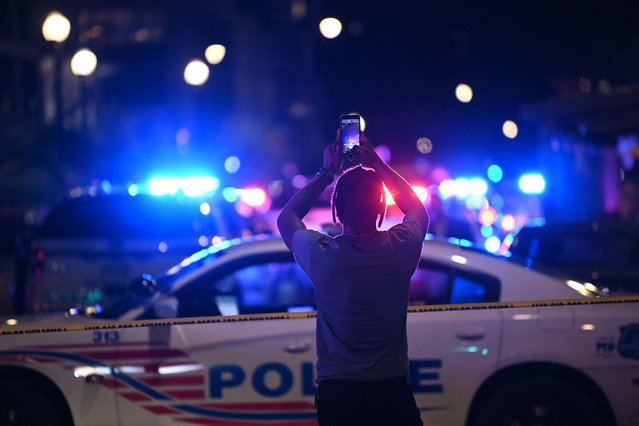 A man uses his phone in front of police cars blocking a street after a shooting at a restaurant in Washington, DC, on July 22, 2021. (Photo by Brendan Smialowski/AFP Photo)
