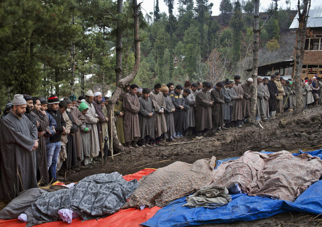 Kashmiri Muslim villagers pray by the bodies of landslide victims during a joint funeral in the village of Laden, some 45 kilometers (28 miles) west of Srinagar, Indian-controlled Kashmir, Tuesday, March 31, 2015. Floodwaters were receding in Kashmir, but residents of the main city of Srinagar were bracing for more trouble after predictions of additional rain in the next few days. (Photo by Dar Yasin/AP Photo)