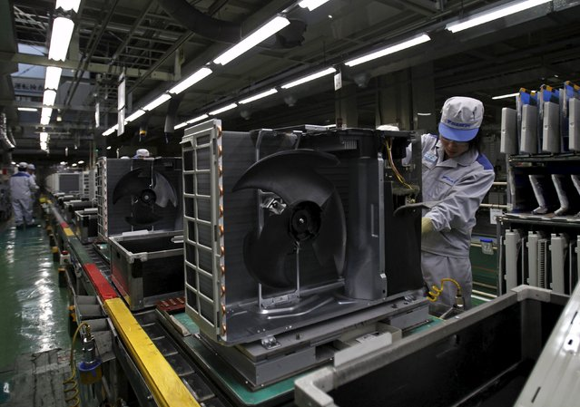 An employee of Daikin Industries Ltd works the production line of outdoor air conditioning units at the company's Kusatsu factory in Shiga prefecture, western Japan March 20, 2015. As Japan heads into the season of peak demand for room air-conditioners, Daikin managers have been tasked with figuring out how to boost output by some 20 percent at the 45-year-old Kusatsu plant that six years ago the company had almost given up on as unprofitable. (Photo by Yuya Shino/Reuters)
