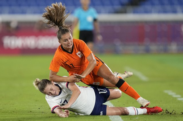United States' Abby Dahlkemper, left, and Netherlands' Lieke Martens fall while fighting for the ball during a women's quarterfinal soccer match at the 2020 Summer Olympics, Friday, July 30, 2021, in Yokohama, Japan. (Photo by Silvia Izquierdo/AP Photo)