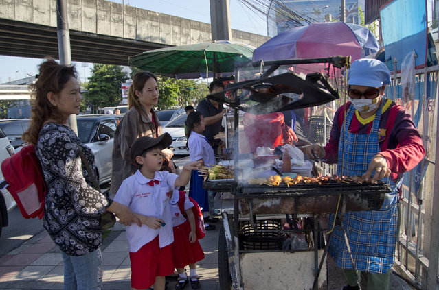 In this Thursday, Novenber 1, 2018, photo, school children gather around street vendors outside their school in Bangkok, Thailand. A report by the United Nations Food and Agricultural Organization released Friday, Nov. 2,  says some 486 million people are malnourished in Asia and the Pacific, and progress in alleviating hunger has stalled. (Gemunu Amarasinghe/AP Photo)
