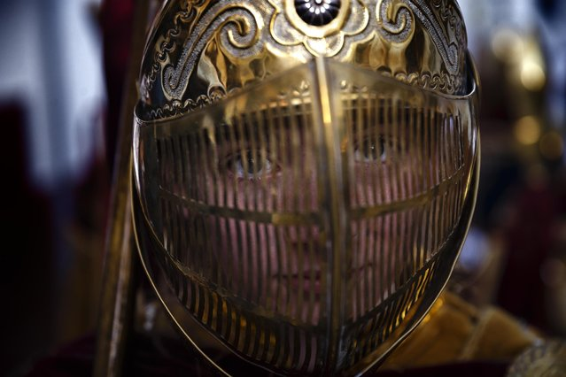 In this photo taken on Thursday, April 2, 2015, a penitent wears a golden helmet, part of her costume of Roman empire's soldier, as she takes part on the 'Estacion Penitencial de Nuestro Padre Jesus Nazareno Cautivo' Holy Week procession in Arriate, Spain. (Photo by Daniel Ochoa de Olza/AP Photo)