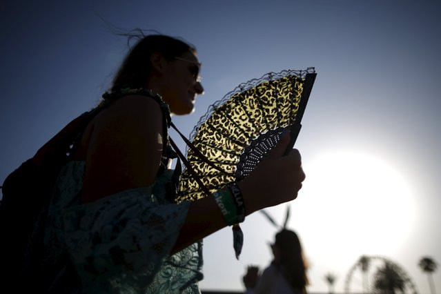 A woman fans herself as she walks through the Coachella Valley Music and Arts Festival in Indio, California April 11, 2015. (Photo by Lucy Nicholson/Reuters)