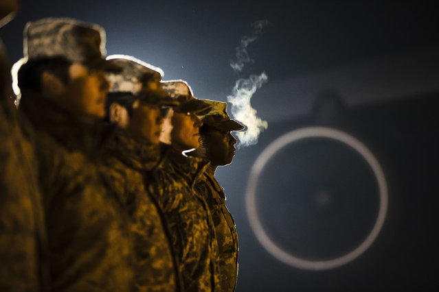 Members of the military wait for an Army carry team to move a transfer case containing the remains of Spc. Isiah L. Booker at Dover Air Force Base, Del., Wednesday, January 11, 2017. According to a statement from the Department of Defense, Booker of Cibolo, Texas, died Jan. 7, in a non-combat related incident while in Jordan supporting Operation Inherent Resolve. (Photo by Matt Rourke/AP Photo)