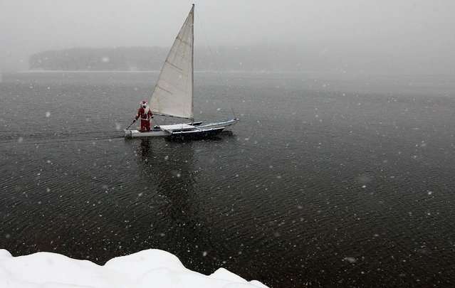 "A member of the ""Skipper"" yacht club, dressed as Santa Claus, sails his trimaran to mark the ending of the sailboat season on the Yenisei River, outside Russia's Siberian city of Krasnoyarsk, on December 18, 2013. (Photo by Ilya Naymushin/Reuters)"