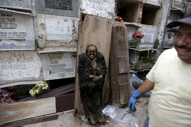 A mummified body leans on a coffin near a grave cleaner (R) during exhumation works at the General Cemetery in Guatemala City, April 15, 2015. (Photo by Jorge Dan Lopez/Reuters)